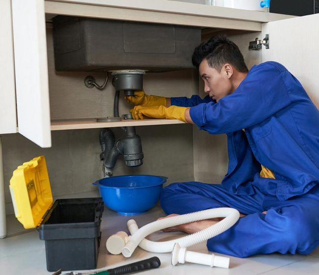 Young Vietnamese plumber checking drain in kitchen